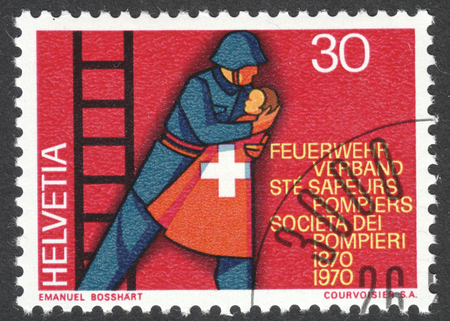 rescuing: MOSCOW, RUSSIA - CIRCA APRIL, 2016: a post stamp printed in SWITZERLAND shows a fireman rescuing a child, dedicated to the 100th anniversary of the Swiss Firemen's Association, circa 1970