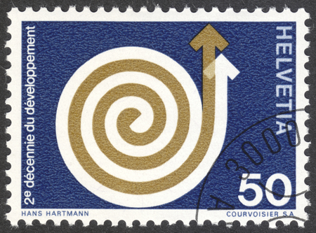 MOSCOW, RUSSIA - CIRCA APRIL, 2016: a post stamp printed in SWITZERLAND shows a rising spiral, devoted to Development Aid, circa 1971 Editorial
