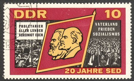 socialist: MOSCOW, RUSSIA - CIRCA JULY, 2016: a stamp printed in DDR shows Flag with Marx and Lenin, the series The 20th Anniversary of the Socialist Unity Party, circa 1966