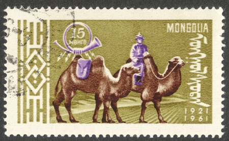 camel post: MOSCOW, RUSSIA - CIRCA AUGUST, 2016: a stamp printed in MONGOLIA shows a postman on Bactrian Camel (Camelus bactrianus), the series The 40th Anniversary of Mongolian Postal Service, circa 1961 Editorial