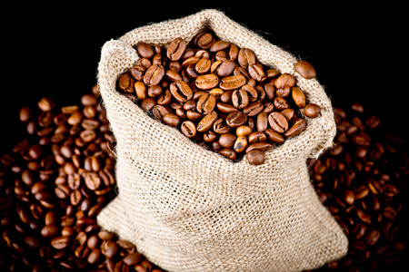 The sack of coffee beans on wooden background