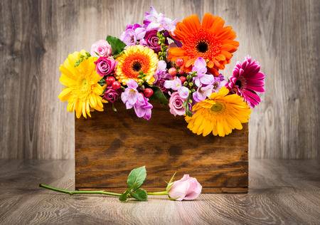 Flowers in the box on wooden background Stock Photo