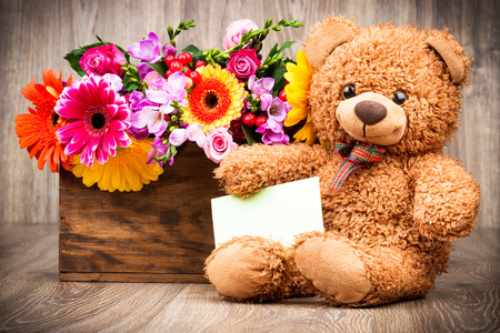 bunch of hearts: Flowers and a teddy bear on wooden background