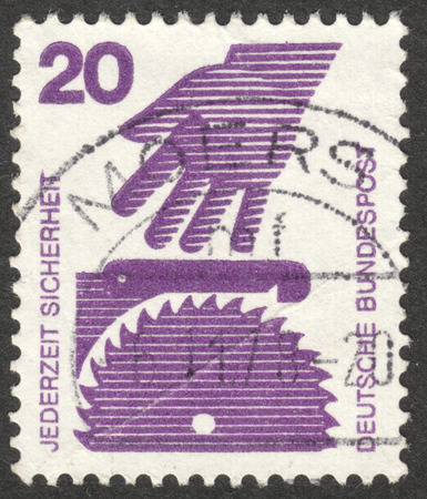 MOSCOW, RUSSIA - CIRCA SEPTEMBER, 2016: a stamp printed in GERMANY shows a hand and a circular saw (Factory Safety), the series Prevent accidents, circa 1971 Editorial
