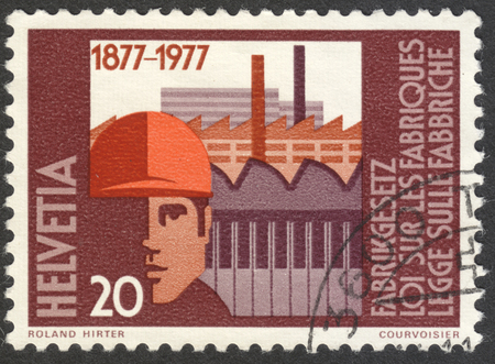 edicto: MOSCOW, RUSSIA - CIRCA JANUARY, 2017: a post stamp printed in SWITZERLAND shows Factory building & worker with safety helmet, the series Factory Law, circa 1977
