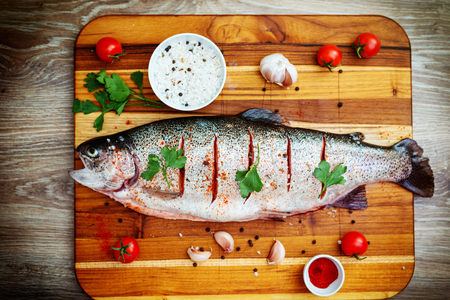 brown trout: Photo of the raw trout on wooden background