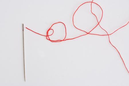 hilo rojo: hilo rojo y aguja en blanco de lino textil
