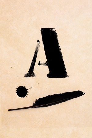 inkblot: Old black, frayed grunge A - letter, inkblot and black feather on brown paper Stock Photo
