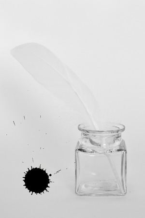 ink pot: white feather, ink pot and black inkblot on white paper