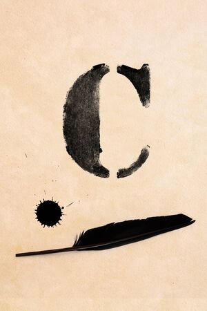 inkblot: Old black, frayed grunge C - letter, inkblot and black feather on brown paper Stock Photo