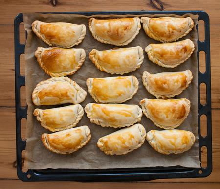 snack food: fresh empanadas - traditional food  on baking tray