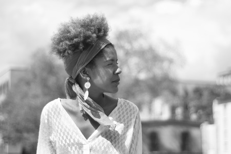 Head shot of young afro american curly woman in urban surrounding - black and white photography