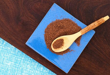 chocolate powder: close up of  a wooden spoon and chocolate powder on wooden background - studio shot  from above