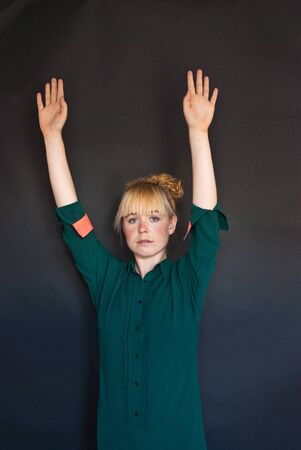 woman hands up: young pretty woman with hands up - studio shot - black background