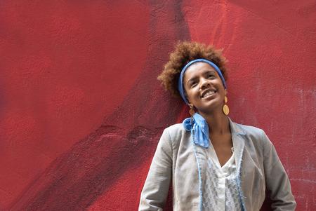 profil: Szef strzał młodych afro amerykański kręcone profilu kobieta przed czerwony mur Zdjęcie Seryjne