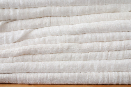 incontinence: stack of eco friendly washeable textile diapers - white textile background Stock Photo