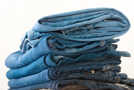 in jeans: Jeans apilados sobre un fondo blanco - tiro del estudio