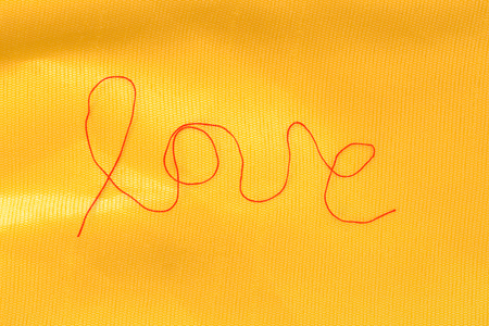 hilo rojo: red thread - love sign - on textured silk background Foto de archivo