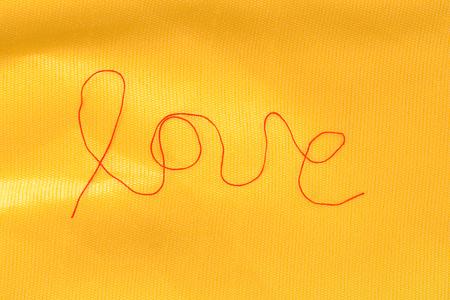 hilo rojo: red thread - love sign - on textured silk background Foto de archivo