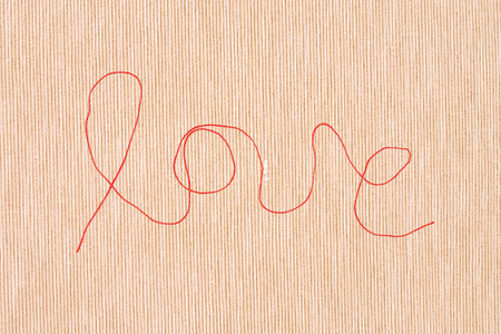 hilo rojo: red thread - love sign - on textured linen background