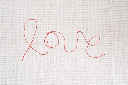 hilo rojo: hilo rojo - muestra del amor - en el fondo con textura de lino