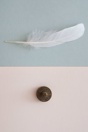eather: white feather and weight on grey paper background