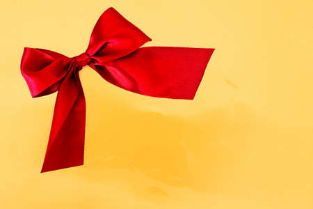 glitzy: red bow on golden background - copy space for text