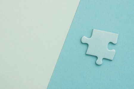 puzzling: isolated blue Puzzle piece on blue paper background