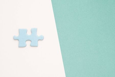 puzzling: isolated blue Puzzle piece on white paper background