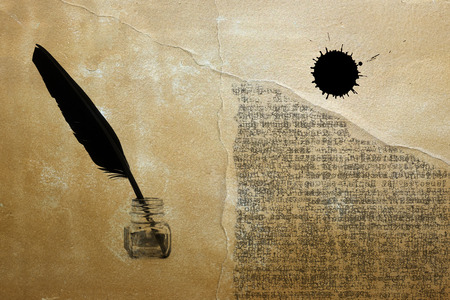 black feather and ink pot on ancient paper background Stock Photo