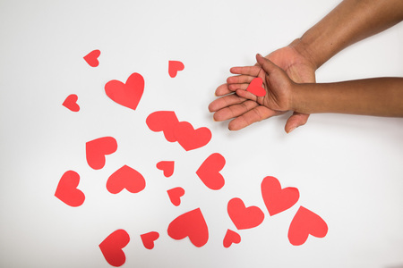 keep in touch: mother and daughters hands on white background - red paper hearts - love symbol  Mothers Day
