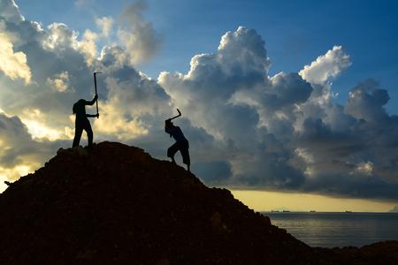 Workers using hoe to dig heap of soil on coastline.