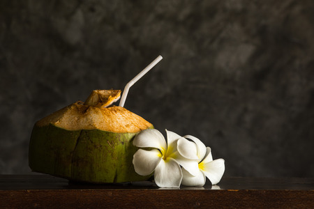 Coconut ornamented with Plumeria on wooden table with concrete wall background.