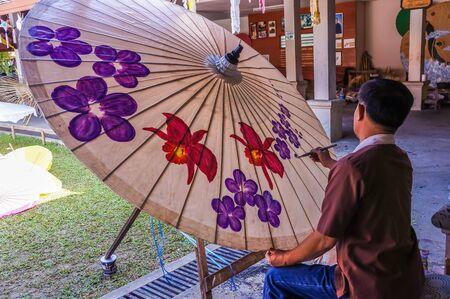 december 25: CHIANGMAI, THAILAND - DECEMBER 25, Man paints flowers on umbrella on December 25, 2013 in Chiangmai, Thailand Editorial