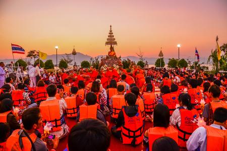 candlelit: PAYAO, THAILAND - FEBRUARY 14, Buddhists  with  monks pay respect to Buddha image  at Buddhist temple on island of Payao lake for Buddhist merit event on February 14, 2014 in Payao, Thailand Editorial