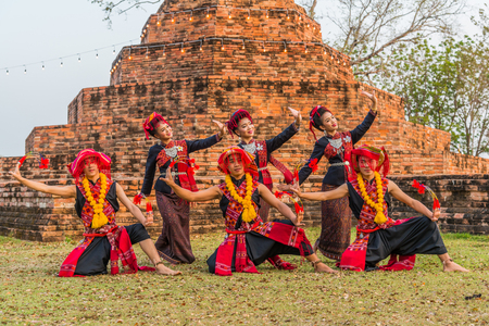 northeastern: KALASIN, THAILAND - FEBRUARY 20, 2016: Girl   and boy dancers with local dress doing Thai Northeastern traditional dance at Yaku Pagoda to celebrate Buddism event in Kalasin