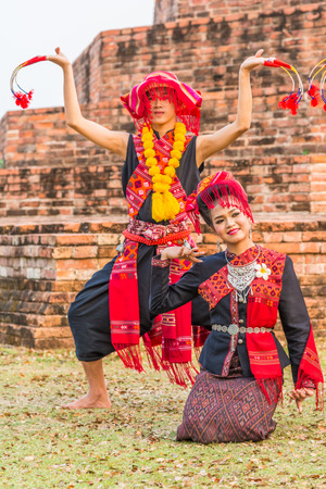 KALASIN, THAILAND - FEBRUARY 20, 2016: Girl   and boy dancers with local dress doing Thai Northeastern traditional dance at Yaku Pagoda to celebrate Buddism event in Kalasin