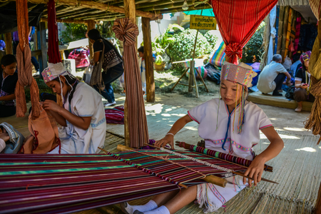 weavers: CHIANGMAI, THAILAND - JANUARY 24, 2015: Hill tribe girl is demonstrating weaving in 22nd Traditional Skirt Fabric and The Indigenous Product and Culture Festival in Mae Chaem of  Chainagmai, Thailand