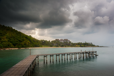 Wooden bridge on sea with rain clouds in public beach Stock Photo