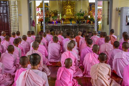 DAWEI, MYANMAR - JULY 11, 2015: Nuns in pink robes chanting in front of Buddha Image in Buddhist temple in Dawei of Myanmar.
