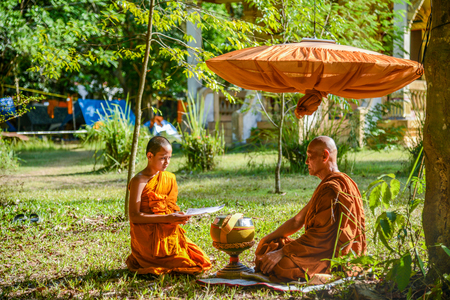 KRABI, THAILAND - MAY 2, 2015: Novice monk chanting in front of senior monk in Lanta island of Krabi, Thailand