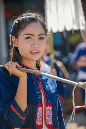 CHIANGMAI, THAILAND - JANUARY 25, 2015: Indigenous girl holding counterpoise with 2 enameled basin of food in parade of 22nd Traditional Skirt Fabric and The Indigenous Product and Culture Festival in Mae Chaem, Chiangmai, Thailand Editorial