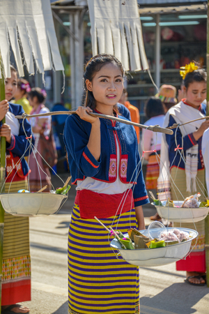 CHIANGMAI, THAILAND - JANUARY 25, 2015: Indigenous girl holding counterpoise enameled basin of food in parade of 22nd Traditional Skirt Fabric and The Indigenous Product and Culture Festival in Mae Chaem, Chiangmai, Thailand