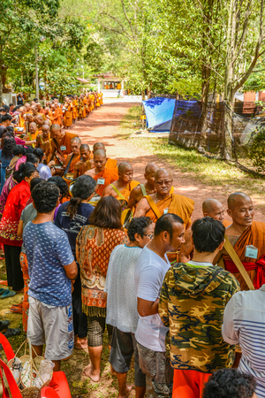 KRABI, THAILAND - MAY 3, 2015: Thai Buddhists offering food to monks alms-bowl in Lanta island of Krabi, Thailand