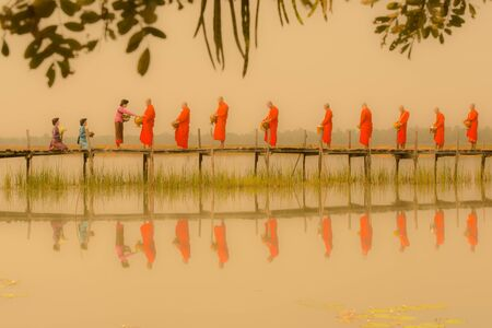 Mahasarakham, Thailand - February 22, 2016: Three women in traditional clothing prepare and offer alms to the monks on wooden bridge in the morning with foggy environment in Mahasarakham, Thailand Editorial