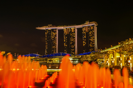 SINGAPORE - JUNE 17, 2014 :  Marina Bay Sands Hotel with light fountains in foreground at night in Singapore Editorial
