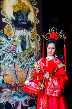 Chachoengsao, Thailand - July 14, 2013 : Beautiful woman with traditional chinese red dress at Chinese shrine door with painting of ancient soldier in Thailand. Editorial