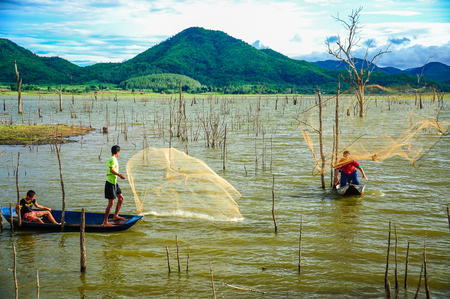 Kanchanaburi, Thailand - July 14, 2012: Fishermen on boat casting fishing net to catch fish in swamp in rural of Thailand