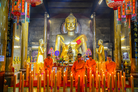 Chachoengsao, Thailand - July 13, 2013: Chinse Buddhist monks lighting the candles to worship golden Buddha Image in chinese shrine in Chachoengsao, Thailand
