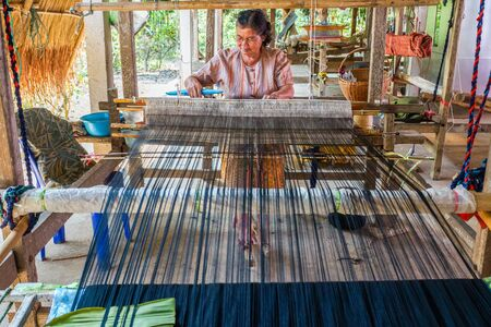 Chiangrai, Thailand - February, 24, 2013: Woman in rural weaving cotton in her own house, this is the second occupation in addition to agriculture in Chiangrai, Thailand Editorial